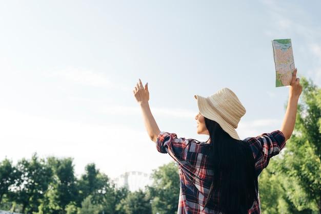 Vista posterior de la mujer levantó su brazo con mapa de retención mirando a otro lado