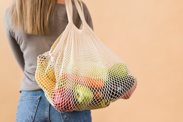 Vista posterior mujer llevando bolsa reutilizable con comestibles