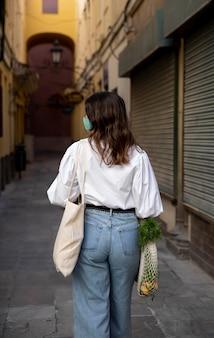Vista posterior de la mujer con mascarilla y bolsas de la compra.