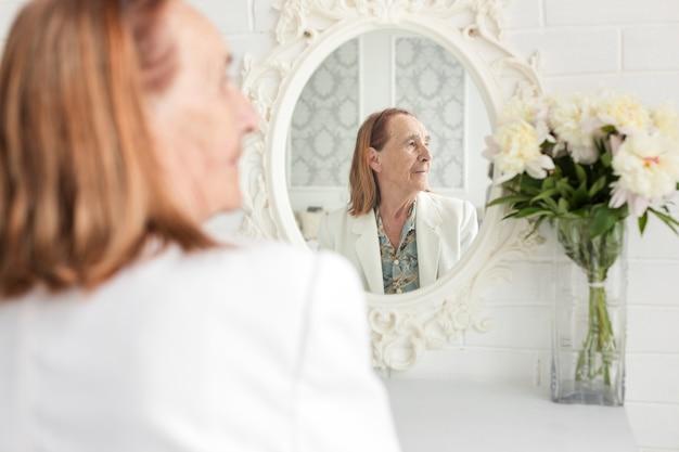 Vista posterior de la mujer mayor que se sienta delante del espejo que mira lejos