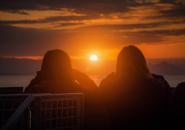 Vista posterior de la mujer de los pares del viajero que mira el mar la puesta del sol en shizuoka, japón.