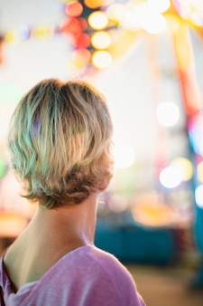 Vista posterior de la mujer en el parque de atracciones