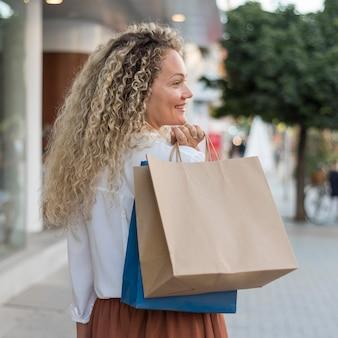 Vista posterior de la mujer con el pelo rizado llevando bolsas de la compra.