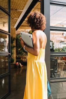 Vista posterior de la mujer con el pelo rizado que sostiene el ordenador portátil