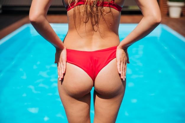 Vista posterior mujer de pie en la luz del sol