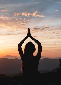 Vista posterior de la mujer en pose de yoga durante la puesta de sol