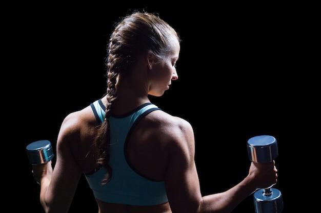 Vista posterior de la mujer que ejercita con pesas de gimnasia