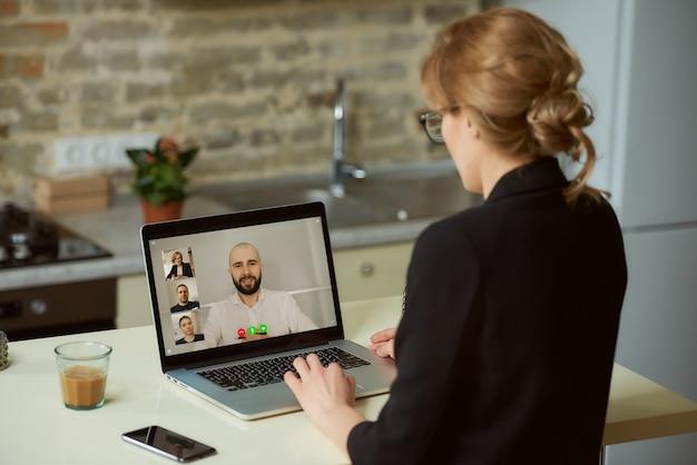 Una vista posterior de una mujer que habla con sus colegas.