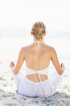 Vista posterior de la mujer que realiza yoga en la playa
