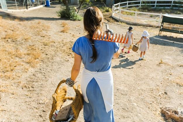 Vista posterior de la mujer que sostiene la cesta y el rastrillo en el hombro que camina con las hijas en campo