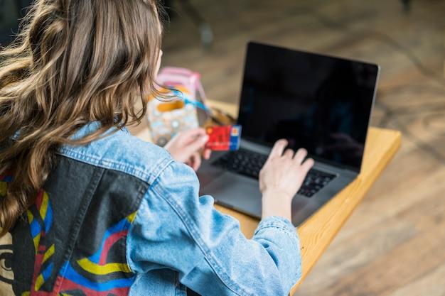Vista posterior de una mujer que sostiene una tarjeta de débito y usa una computadora portátil para hacer compras en línea