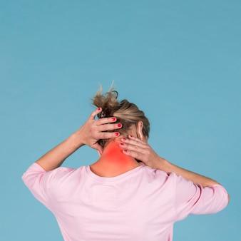 Vista posterior de una mujer que sufre de dolor de cuello frente a un fondo azul