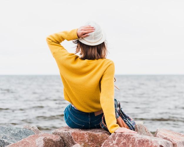 Vista posterior de la mujer que viaja frente al océano