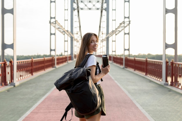 Vista posterior de la mujer que viaja con mochila sosteniendo termo mientras viaja