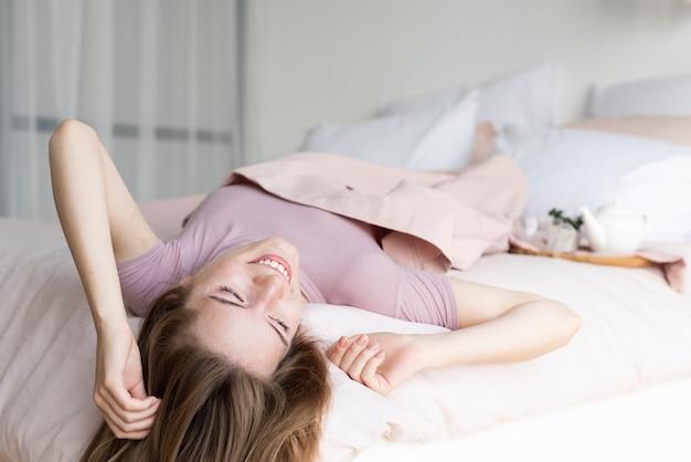Vista posterior mujer quedarse en la cama