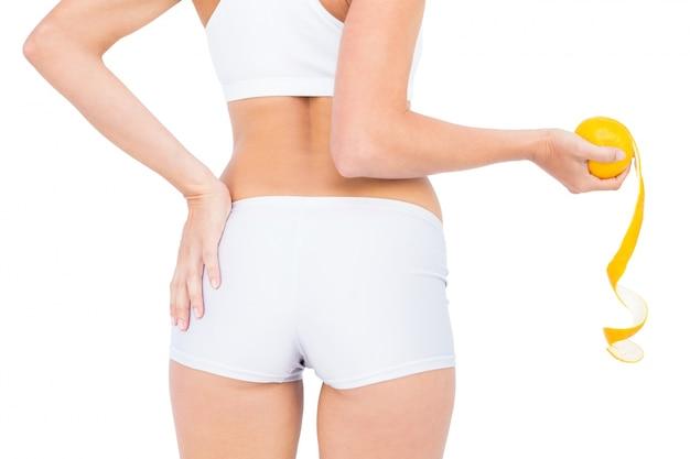 Vista posterior de la mujer en ropa deportiva con naranja