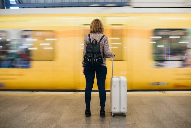 Vista posterior de una mujer rubia esperando en la plataforma del tren