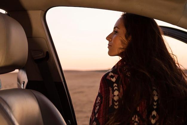 Vista posterior de la mujer saliendo del coche para disfrutar de la naturaleza
