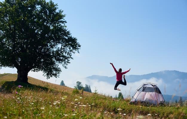 Vista posterior de la mujer saltando en la colina floreciente cerca de la tienda turística y el gran árbol bajo el cielo azul claro en la brillante mañana de verano sobre fondo de montañas brumosas