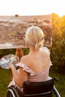 Vista posterior de la mujer en silla de ruedas pintando al aire libre