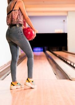 Vista posterior mujer sosteniendo la bola de boliche