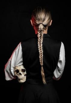 Vista posterior de la mujer sosteniendo el cráneo