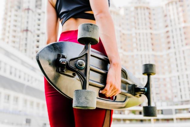 Vista posterior de la mujer sosteniendo un longboard