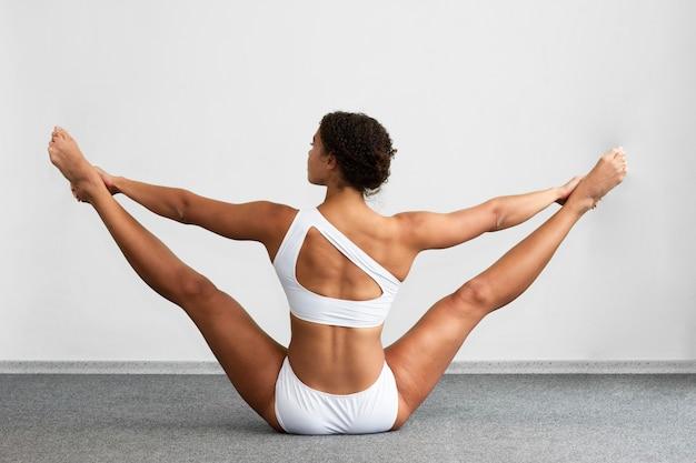 Vista posterior mujer sosteniendo las piernas separadas