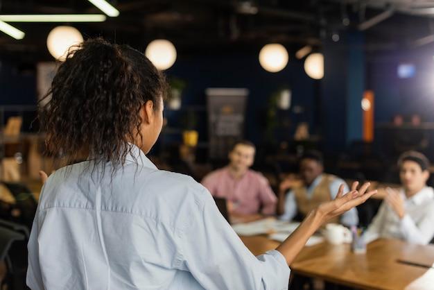 Vista posterior de la mujer sosteniendo una reunión en el trabajo con colegas