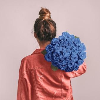 Vista posterior de la mujer, sosteniendo rosas azules clásicas