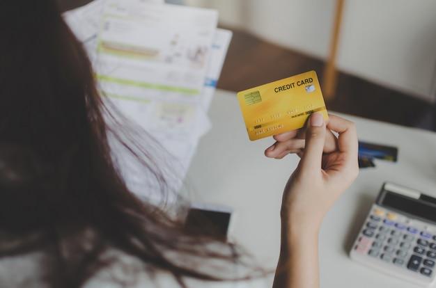 Vista posterior de la mujer con tarjeta de crédito y análisis con facturas de costos del presupuesto familiar en la oficina en casa
