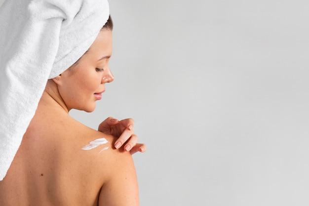 Vista posterior de la mujer con una toalla en la cabeza aplicando crema sobre la piel
