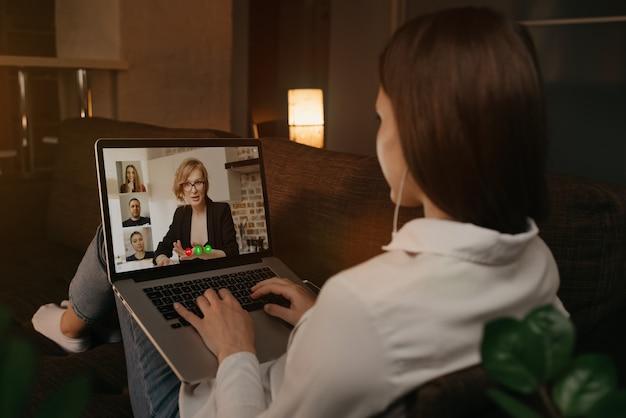 Vista posterior de una mujer tumbada en su casa en un sofá hablando con su jefe y otros colegas en una llamada de video en una computadora portátil. la empresaria habla con sus compañeros de trabajo en una conferencia por webcam. un equipo que tiene una reunión.