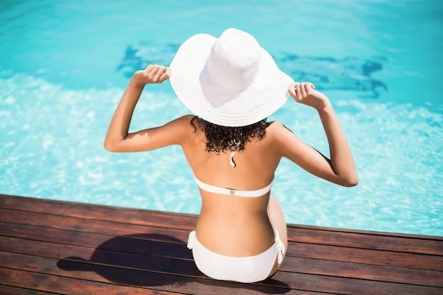 Vista posterior de la mujer vestida con bikini blanco y sombrero sentado cerca de la piscina