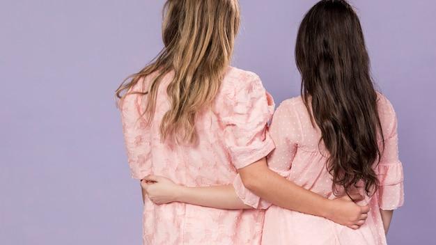Vista posterior de mujeres abrazándose como un signo de hermandad con espacio de copia
