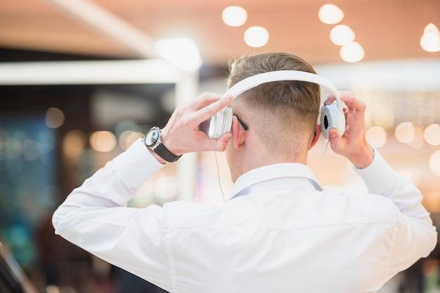 Vista posterior de una música que escucha del hombre joven en el auricular blanco