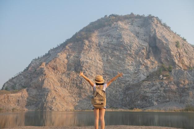 Vista posterior de la niña asiática admirando la hermosa vista de las montañas rocosas y el lago