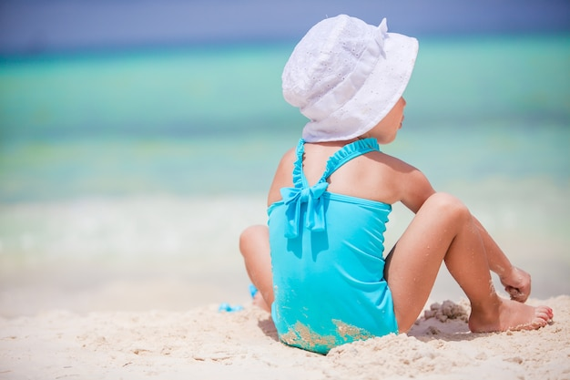 Vista posterior de la niña juega en la playa
