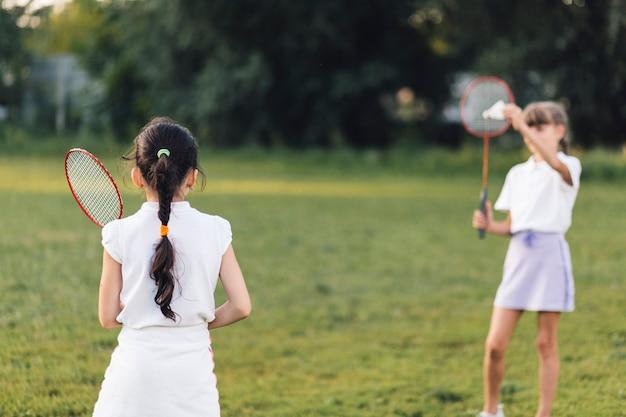 Vista posterior de la niña jugando al bádminton con su amiga