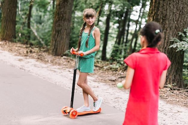 Vista posterior de la niña mirando a su amiga de pie en empuje scooter