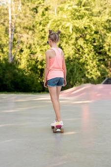 Vista posterior de la niña montando patineta
