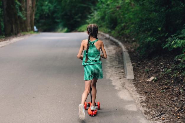 Vista posterior de una niña montando scooter en carretera recta