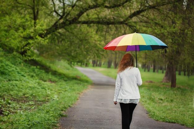 Vista posterior de la niña bajo un paraguas brillante, caminando bajo la lluvia