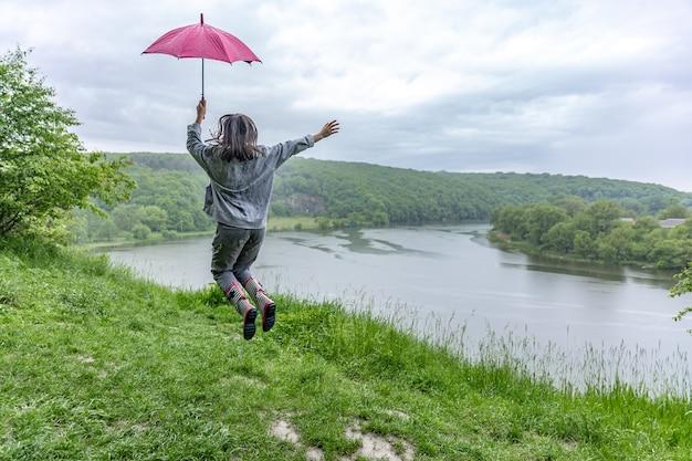 Vista posterior de una niña bajo un paraguas saltando cerca de un lago en una zona montañosa en tiempo lluvioso.