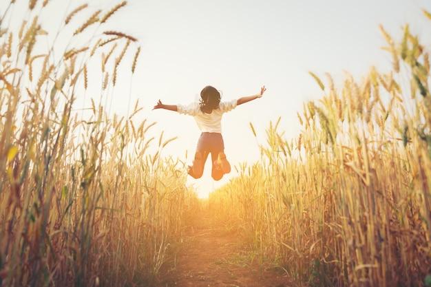 Vista posterior de la niña saltando en la granja de cebada