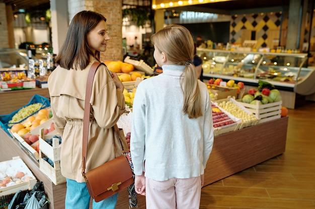 Vista posterior de la niña y su madre decidiendo qué comprar en el supermercado mientras está de pie junto a la pantalla de frutas
