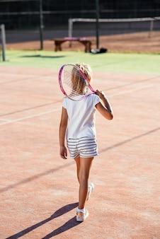 Vista posterior de la niña vestida de blanco uniforme con raqueta de tenis en el hombro caminando en la cancha de tenis al aire libre al atardecer.