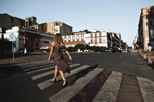 Vista posterior de una niña en vestido de tacón alto en la intersección vacía en la calle de la ciudad