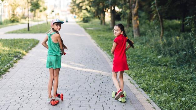 Vista posterior de las niñas montando patinete en el pavimento en el parque