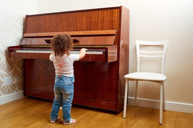 Vista posterior, un niño se para frente al piano y toca una melodía, un pequeño pianista que aprende a tocar el piano, bebé, niño, niño y concepto de música